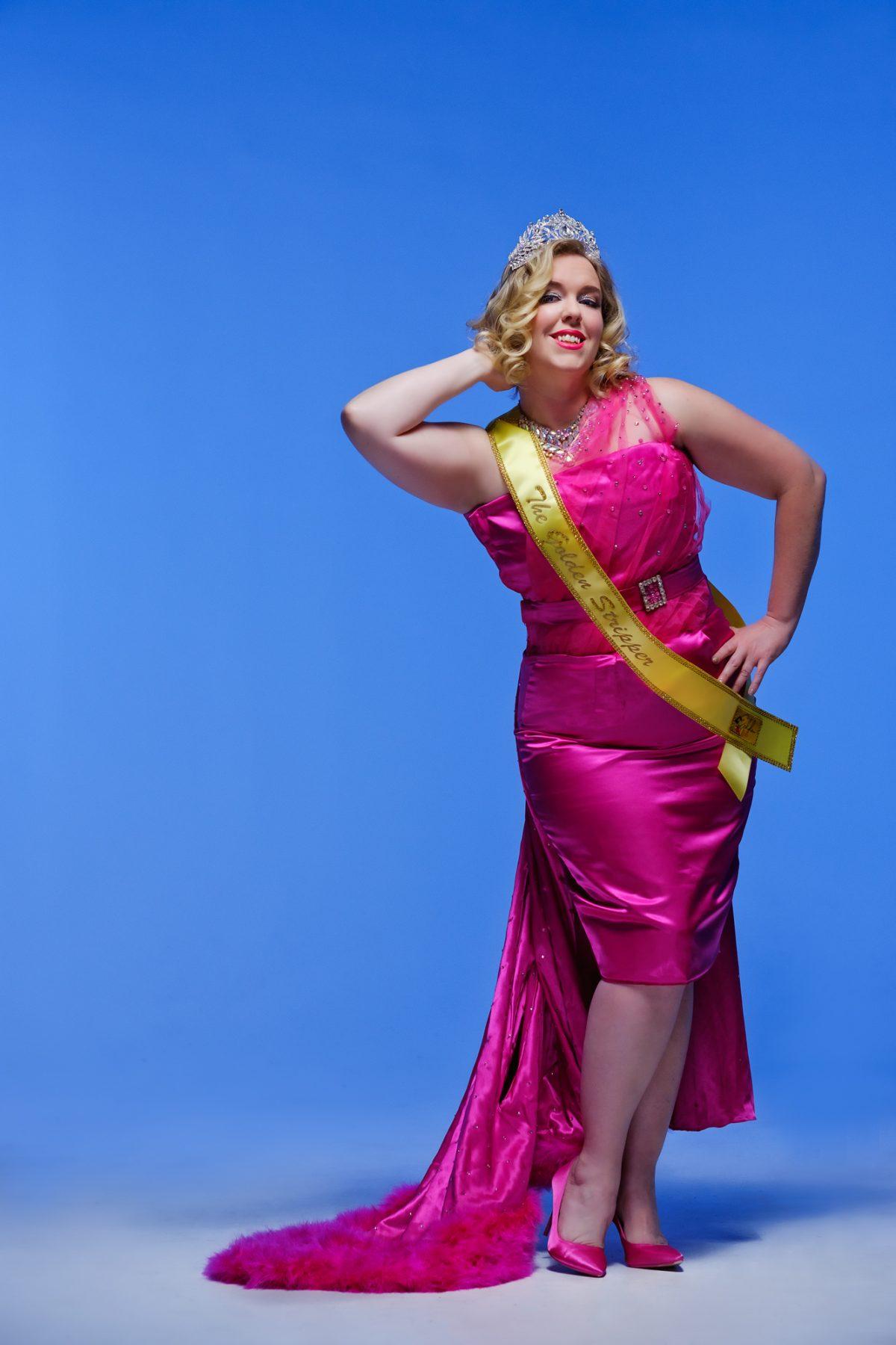 Mae de la Rue wears burlesque costume and Golden Legends Tiara and Sash