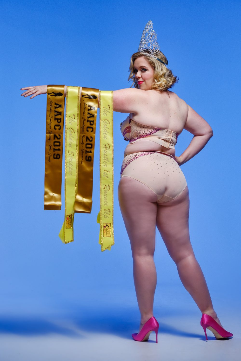 Mae wears skin colour lingerie and holds award sashes and wears a large tiara